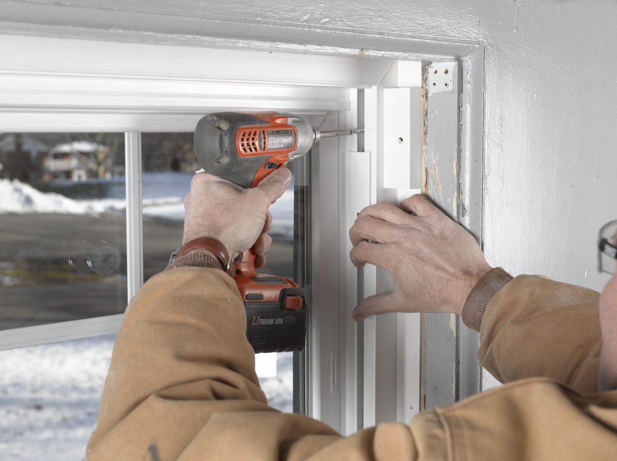 man installing window in home