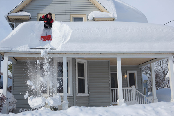 Man Clearing Snow off roof